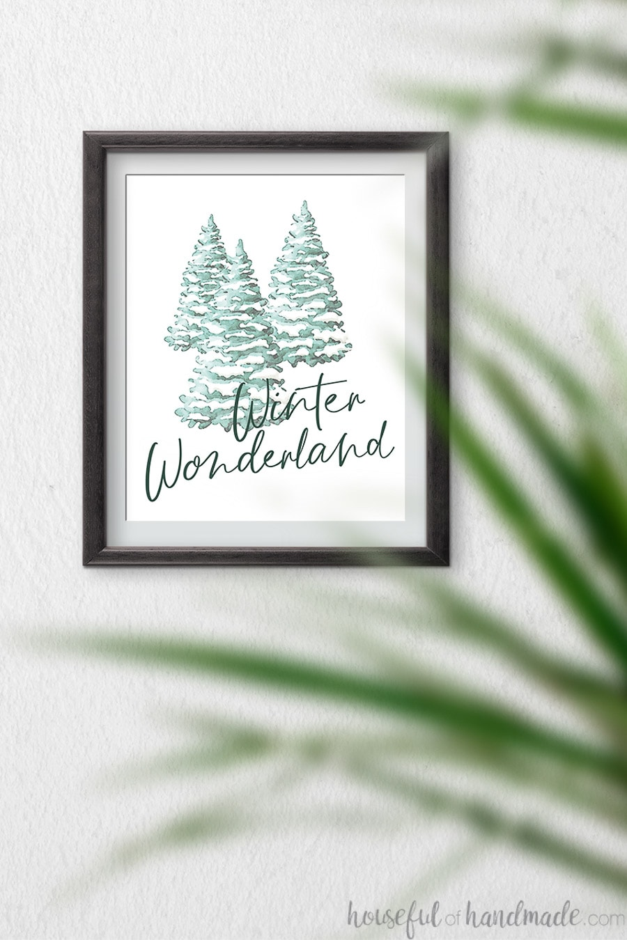 Watercolor Christmas printable with snow covered trees and script writing of Winter Wonderland on it, hanging on a wall.