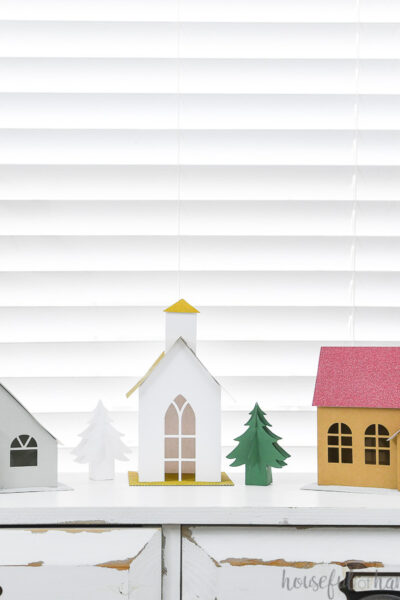 Putz inspired paper Christmas village with 3 different houses and paper Christmas trees on a console table.
