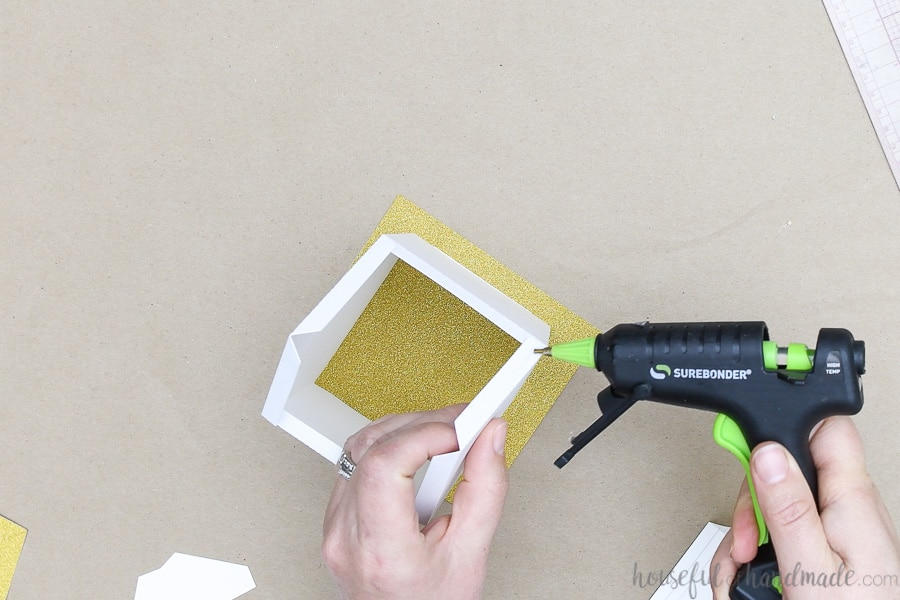 Adding glue to one of the roof tabs on the top of the paper church.