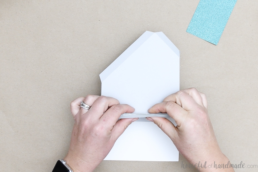 Glueing the tabs on the base of the modern paper house.
