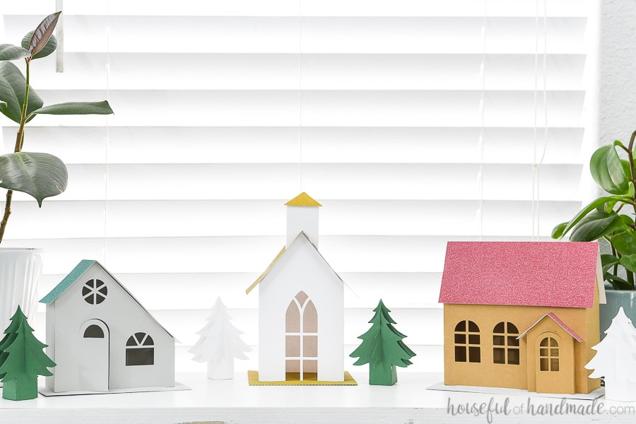 Three paper Christmas houses with paper Christmas trees on a console table.