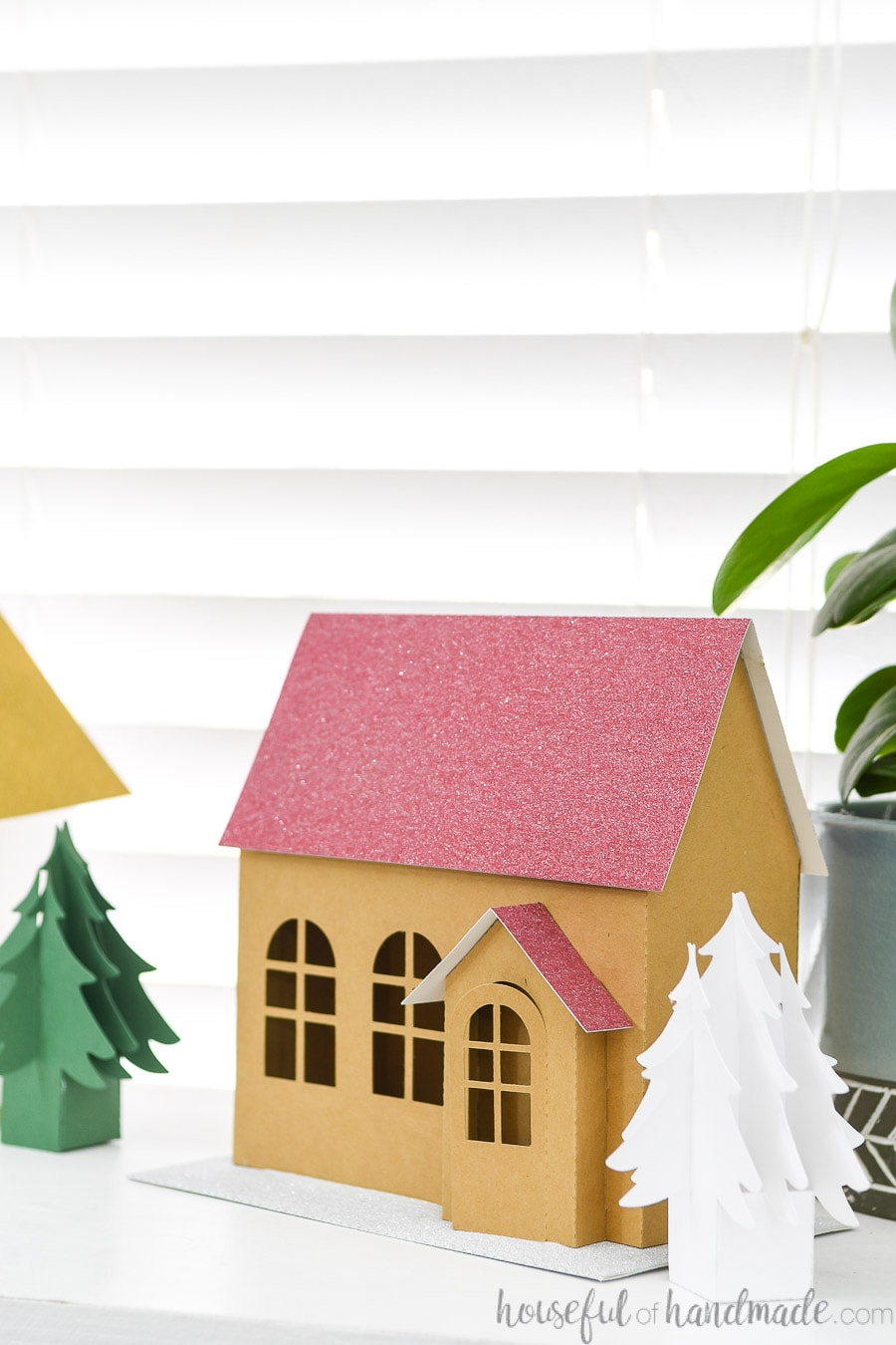 Close up of the brown kraft paper Christmas house with red glitter roof and 3D entryway.