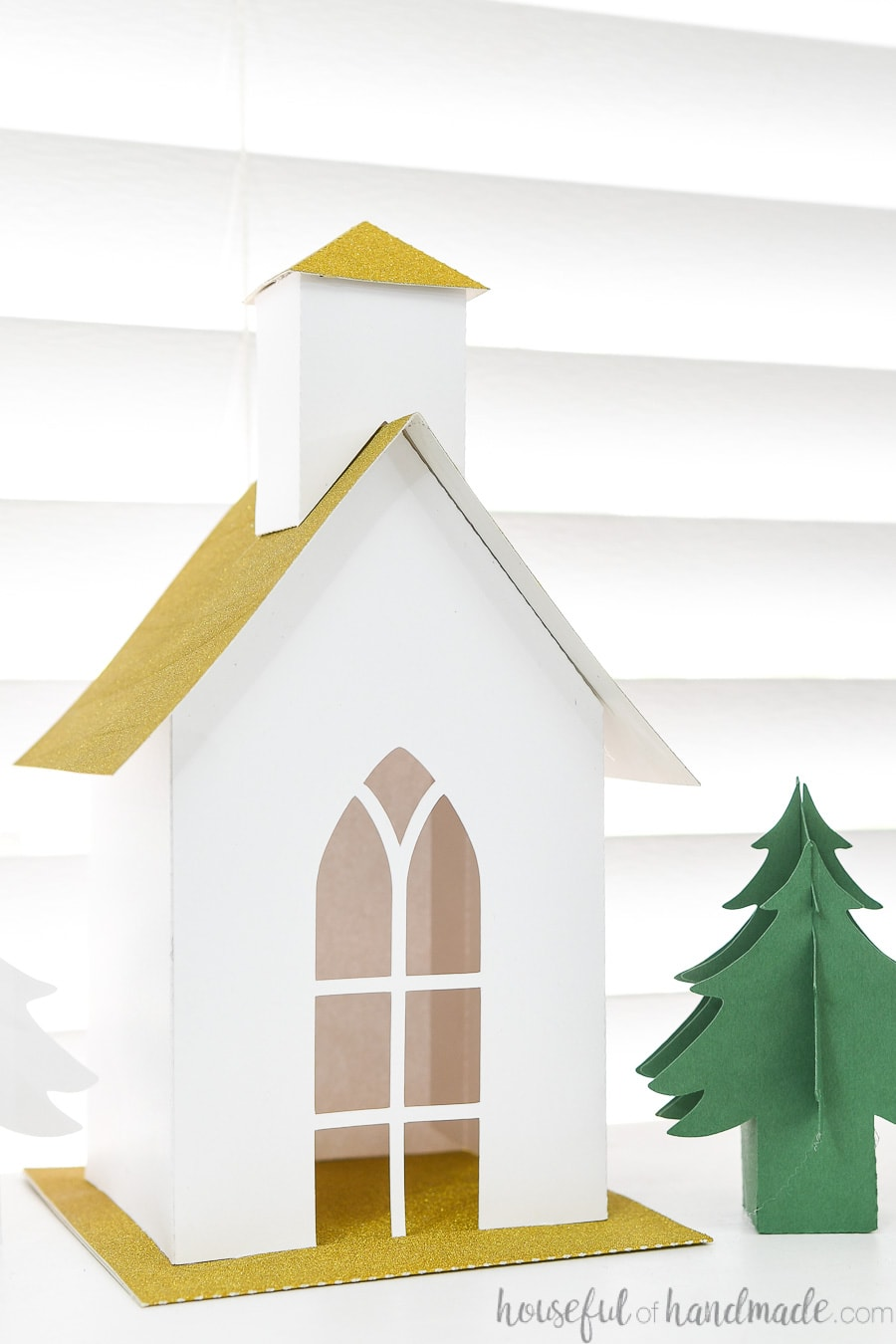 Close up of the paper Christmas church made with white cardstock and gold glitter roof and base next to a green paper Christmas tree.