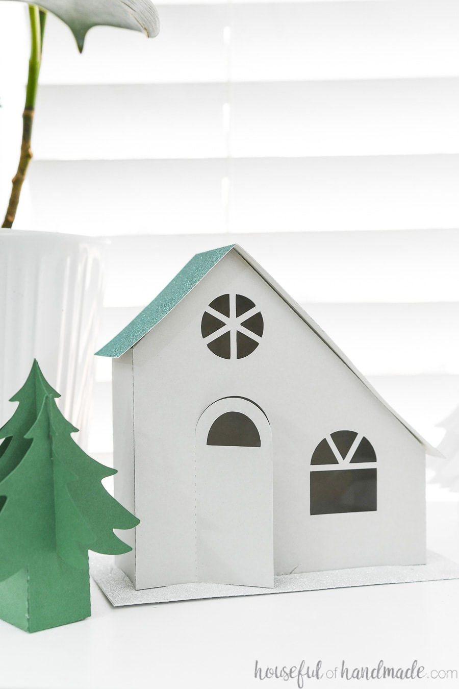 Close up of the gray modern paper house with asymmetrical teal glitter roof.