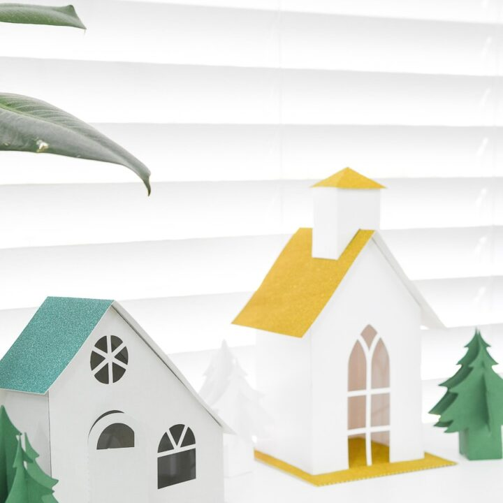 Two paper Christmas houses, one modern style and one church, on a console table.