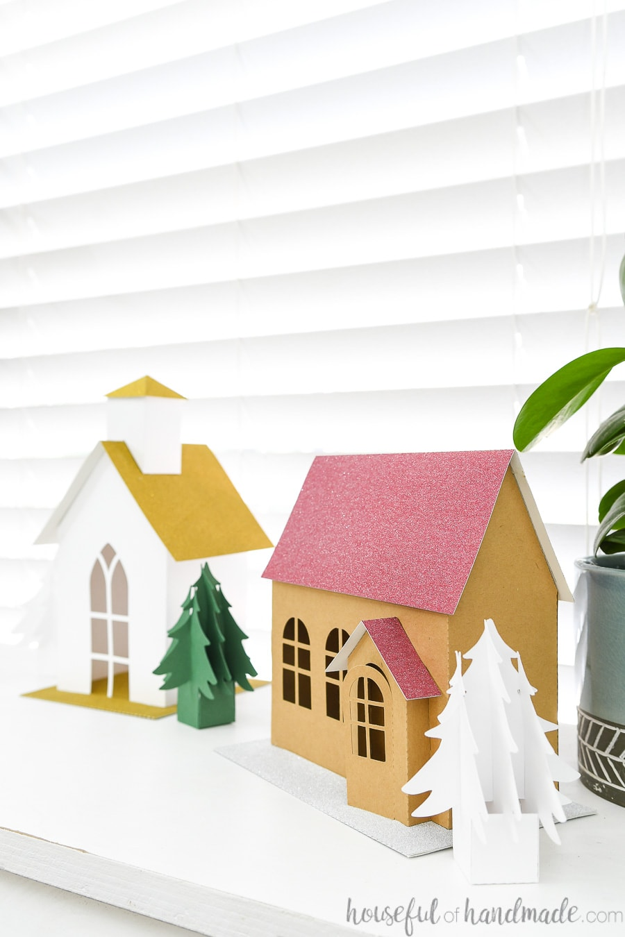 Side view of the classic Christmas house next to the white Christmas church made from paper.