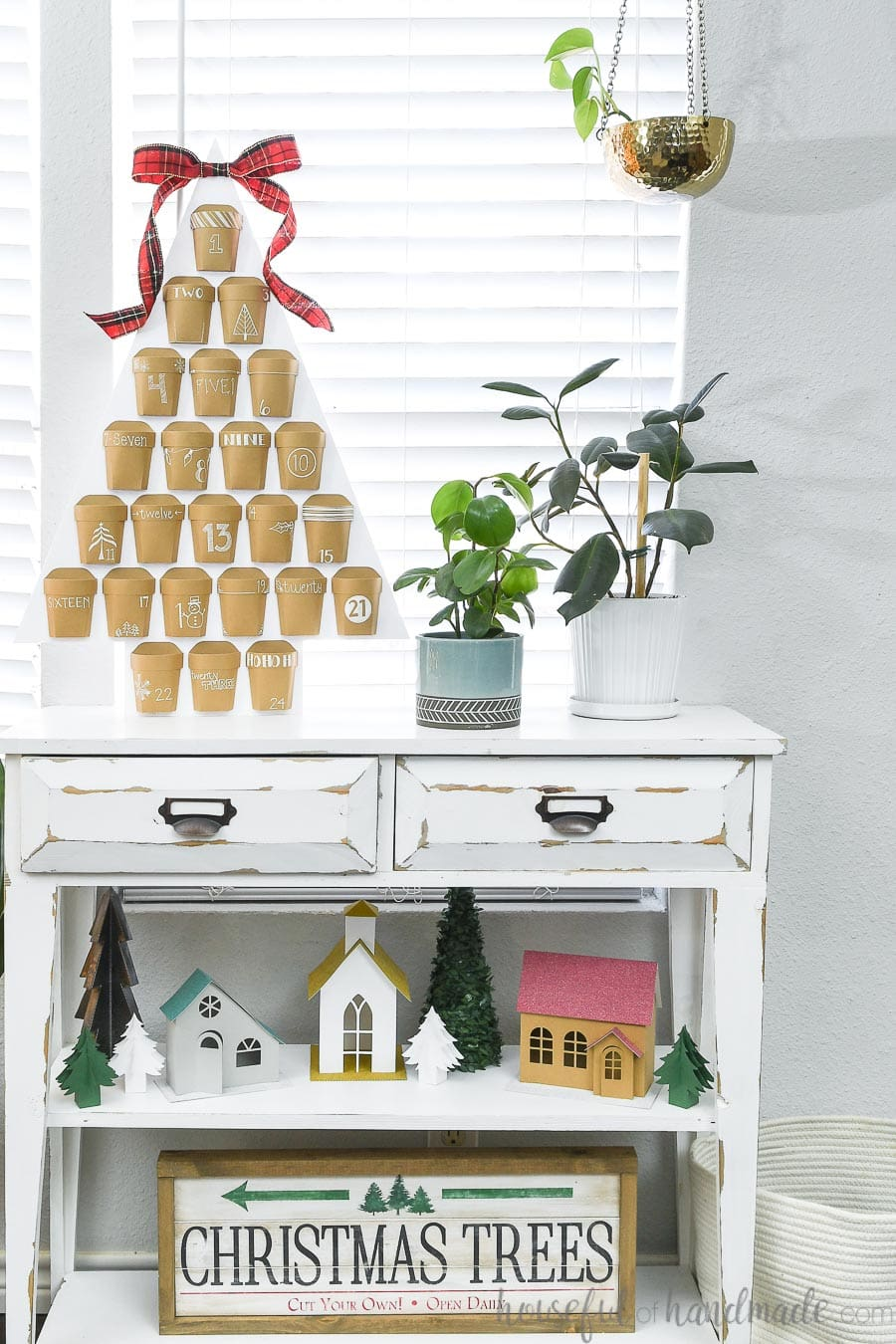 Christmas vignette with a Christmas advent calendar sitting on top of a white console table, a paper Christmas village on the middle shelf and a Christmas tree farm sign on the bottom shelf.