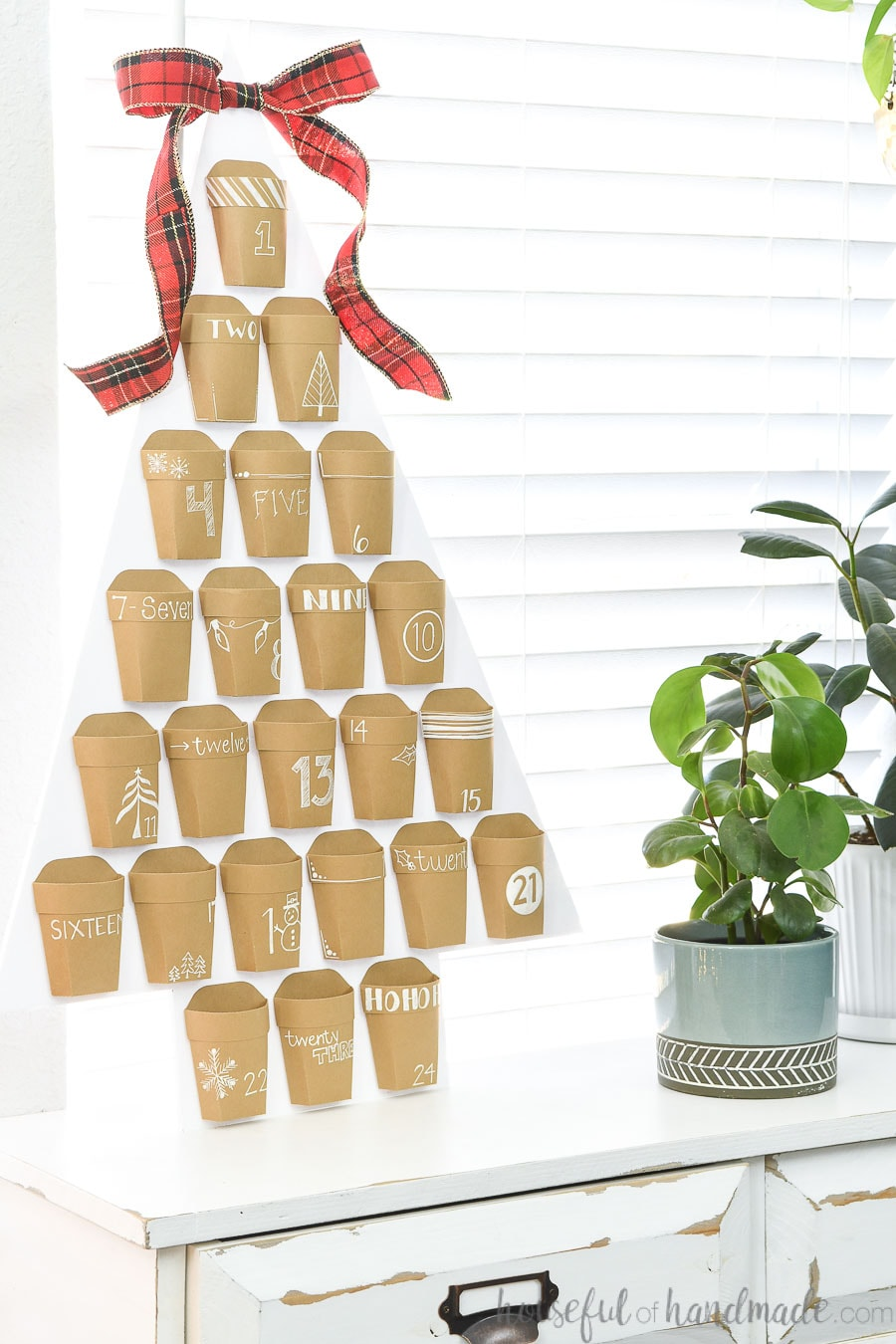 Christmas advent calendar of Kraft paper pockets with white decorations and numbers on a white Christmas tree.