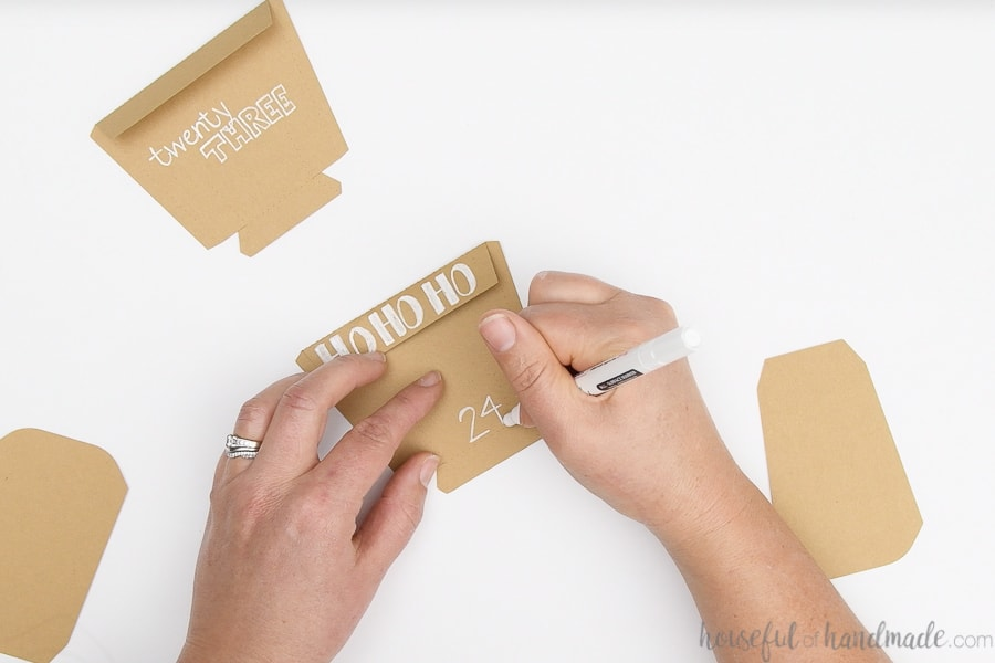Paper pieces cut out of brown Kraft cardstock being decorated with a white paint pen with advent calendar numbers and Christmas pictures.