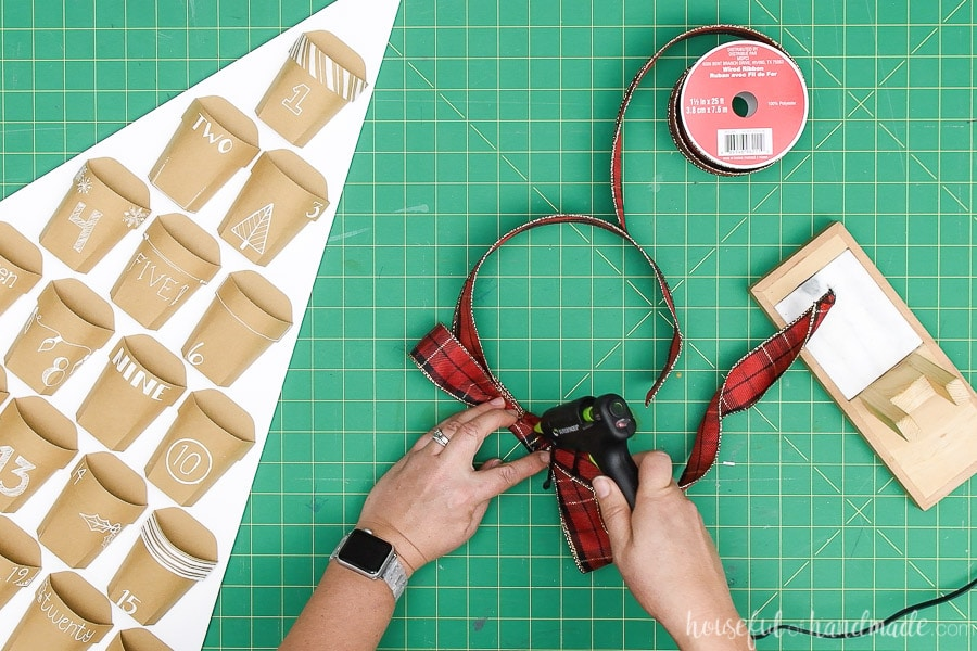 Glueing together a simple bow made from Christmas plaid ribbon.
