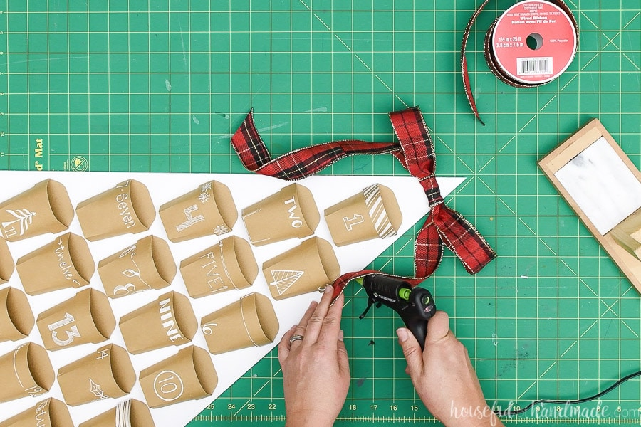Glueing the sides of the ribbon tail to the sides of the Christmas tree advent calendar.