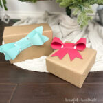 Two gifts under the Christmas tree with bow shaped gift card holders on top.