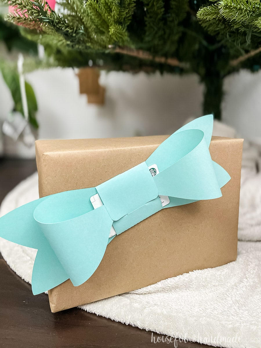 Blue bow shaped gift card holder taped to the front of a present wrapped in brown paper.