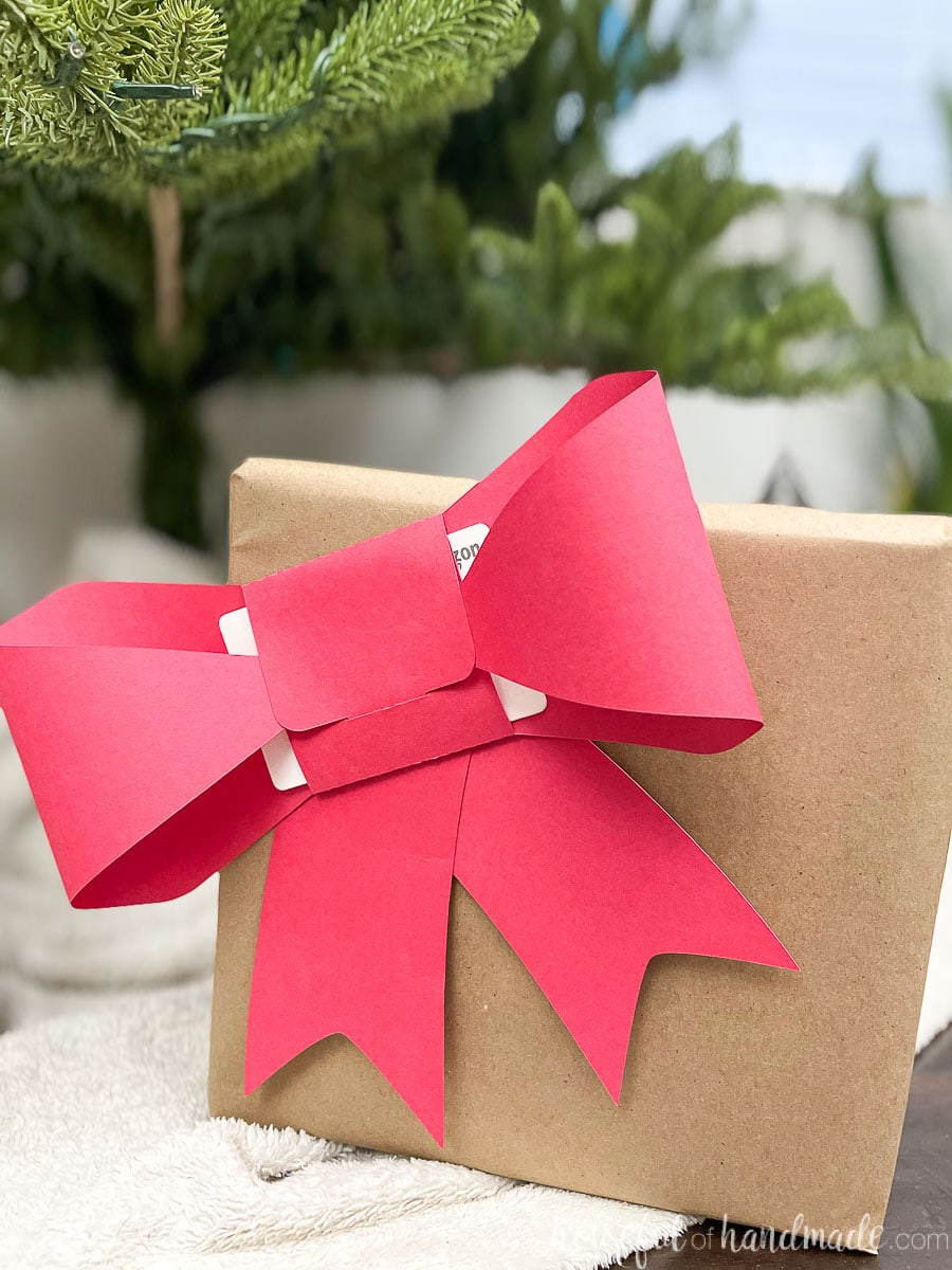 Christmas present wrapped in brown paper with a red paper bow gift card holder on the front.