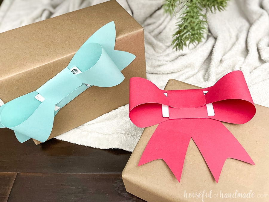 Two presents wrapped in brown paper with large paper bows folded around gift cards taped to the front.