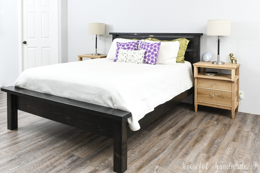 Easy to build queen bed frame stained black with white bedspread and colorful pillows.