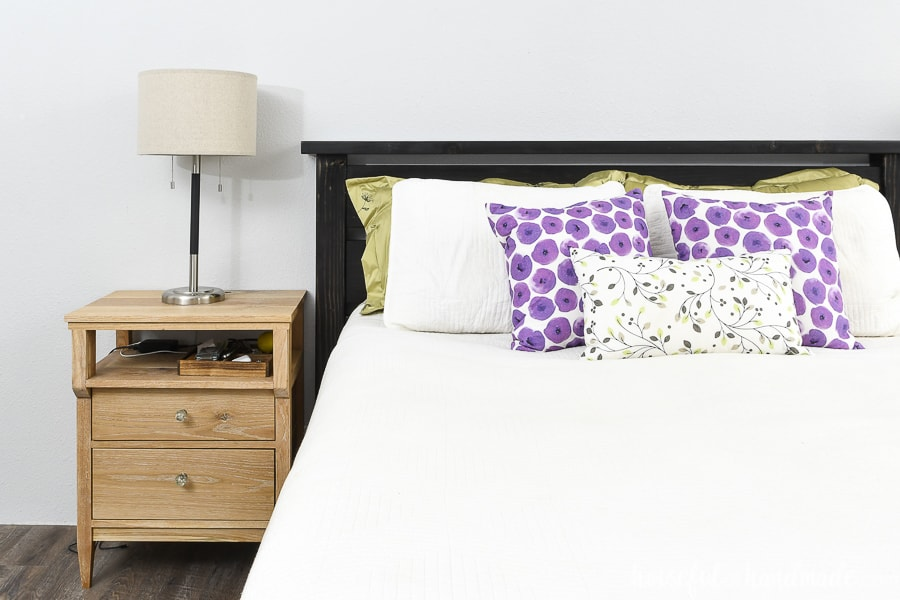 Straight on view of the DIY queen bed frame with a mattress inside and pillows leaning on the headboard.