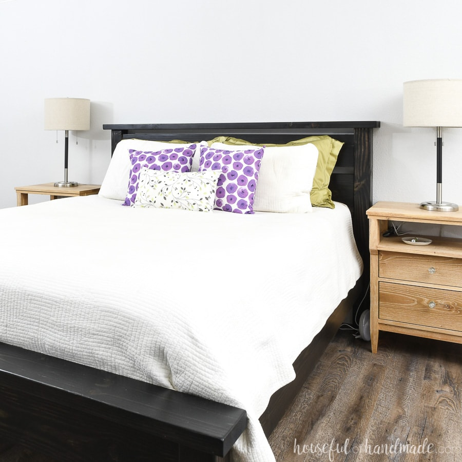 Black wood DIY bed frame for a queen bed dressed in a white comforter and colorful pillows.