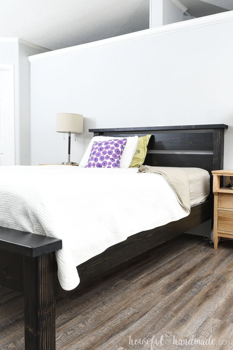 DIY Queen bed frame made from construction lumber and stained black dressed with white linens and colorful throw pillows.