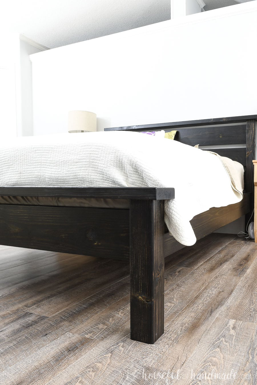 Side view of the black queen bed frame made from inexpensive lumber.