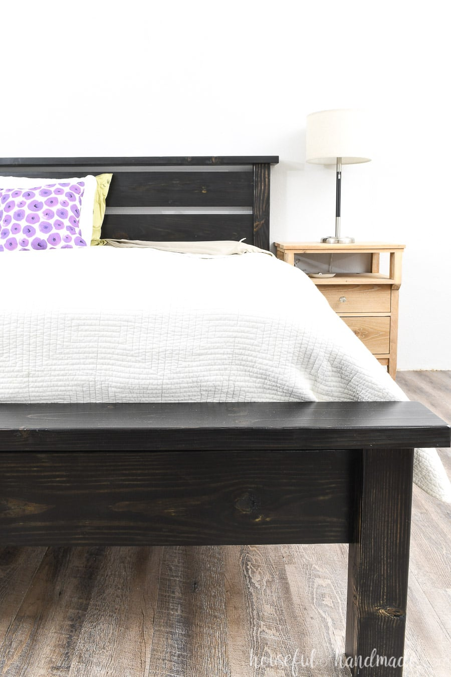 DIY platform bed frame that looks like a traditional bed sitting next to a nightstand.