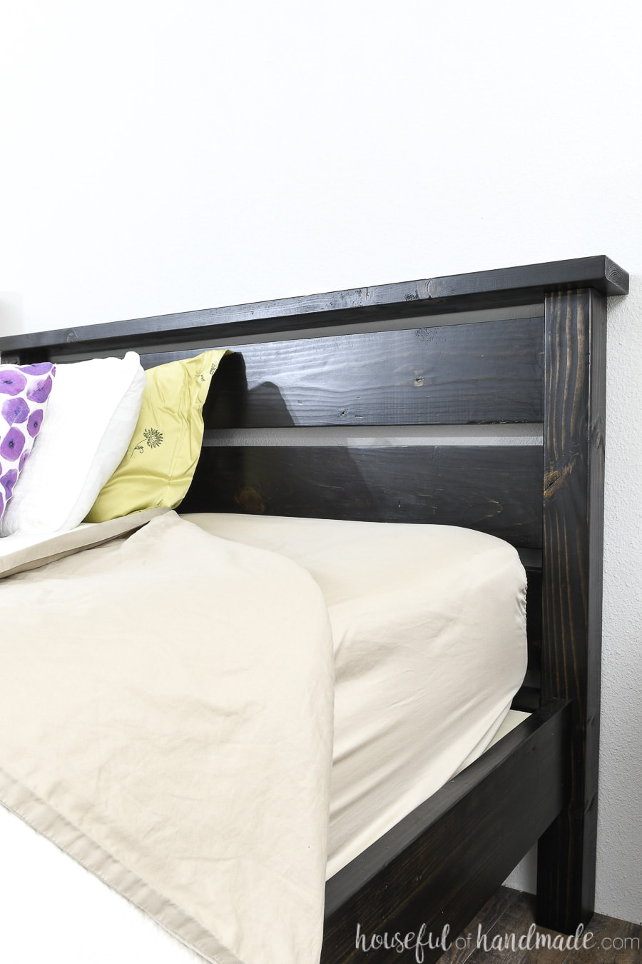 Close up view of the black stained headboard with pillows moved back from the headboard.