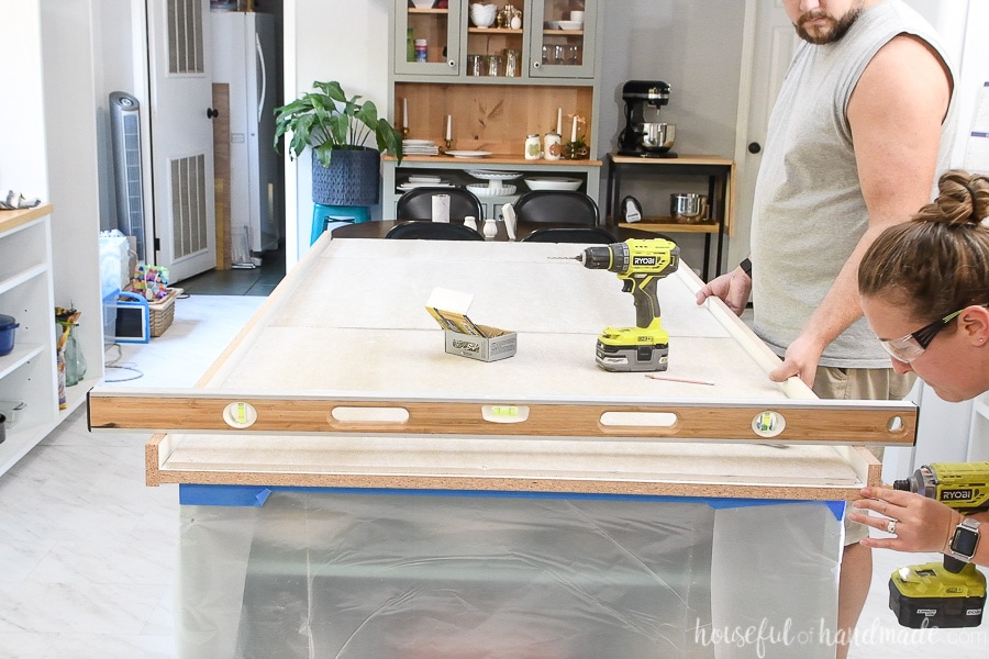 Attaching the form to the second side of the countertop form with a 4' level across the top of both forms so they stay level.