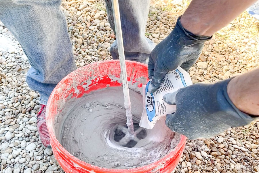 Pouring Flow control into the mostly mixed concrete in the 5 gallon bucket.