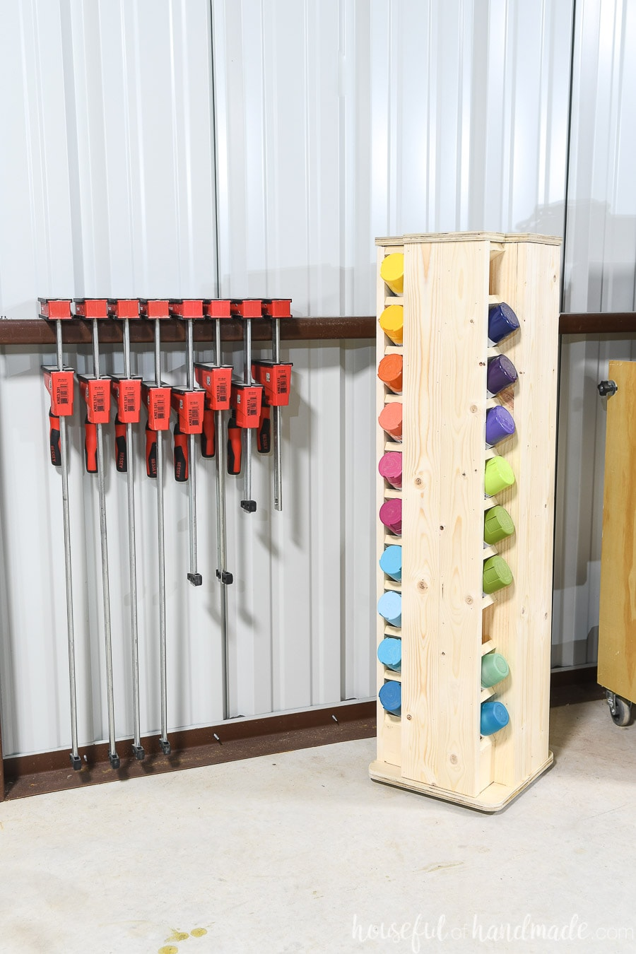 Small rotating spray paint storage cabinet with spray paint cans in organized in a rainbow in a corner next to bar clamps in a shop.