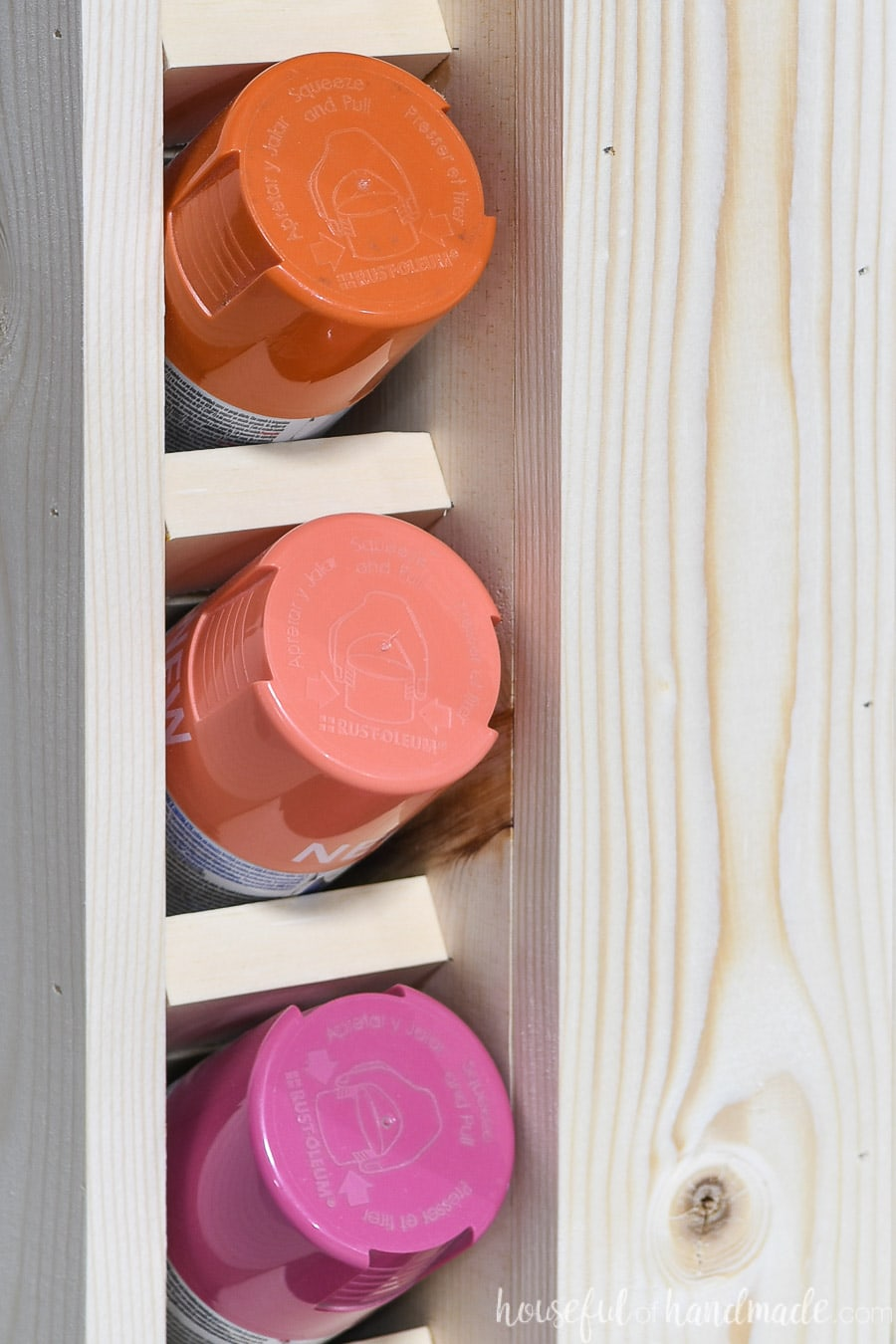 Close up of three paint cans in the slots of the spray paint storage.