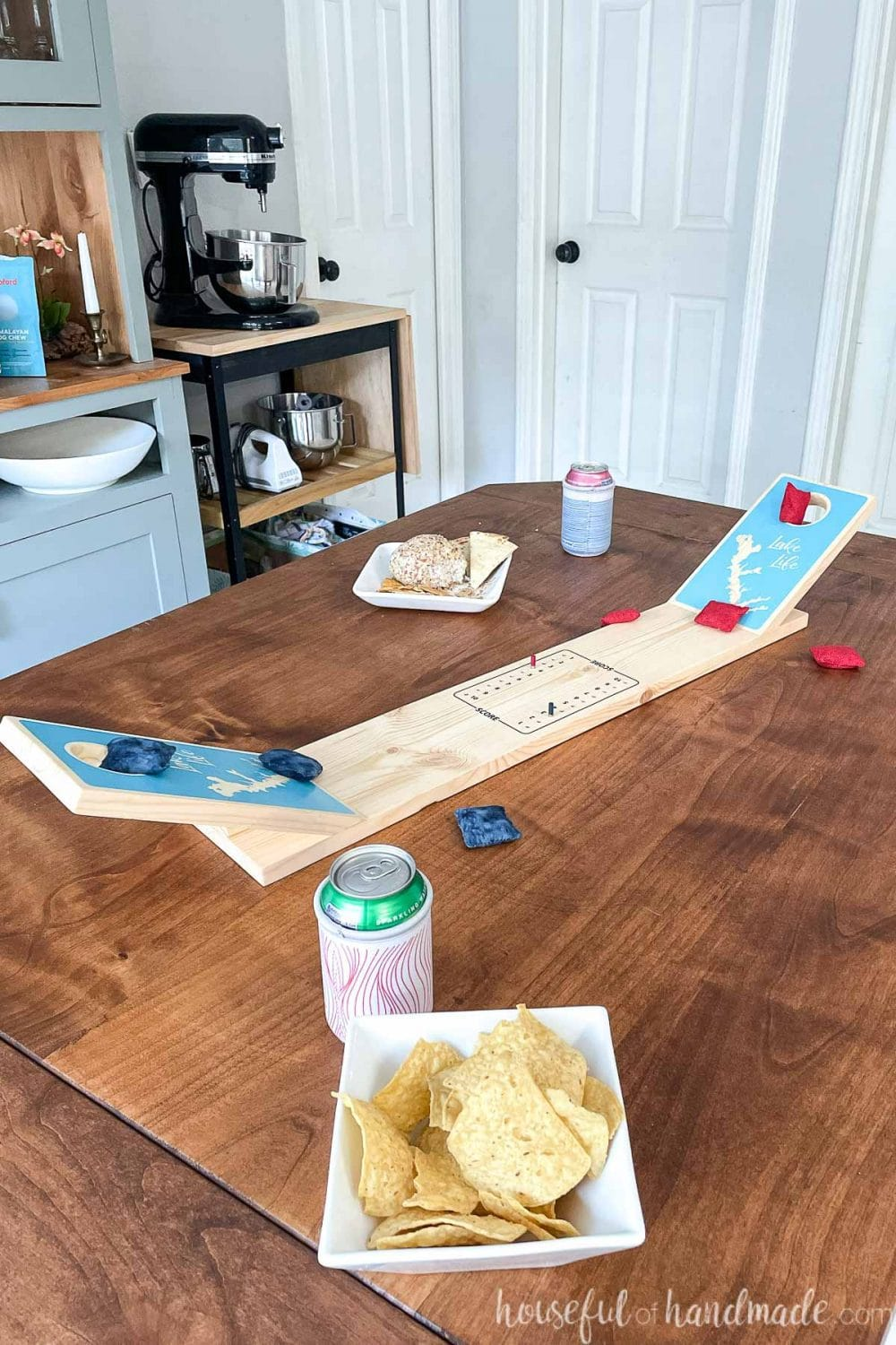 Dining room table with tabletop cornhole game made from wood on the table with drinks and snacks around it.
