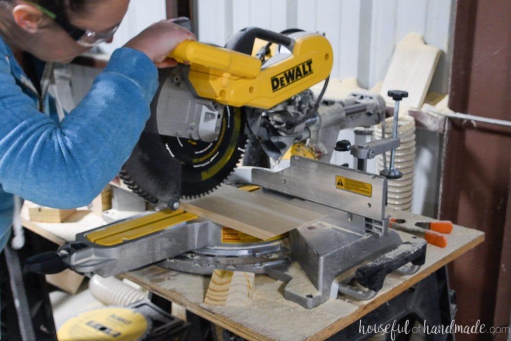 Cutting 1x6 boards for the cornhole game on a Dewalt miter saw.