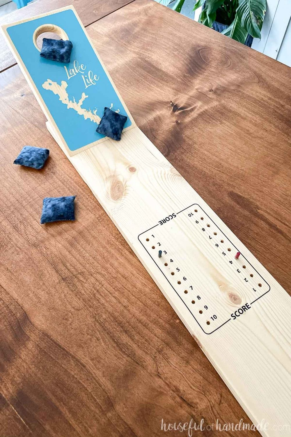 Close up view of the center of the tabletop cornhole game with a peg style scoreboard in the center.