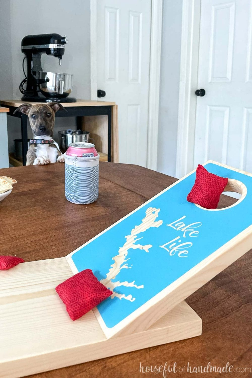 Close up of the one side of the miniature cornhole board on a table with red bean bags on the board and a puppy looking at it in the background.