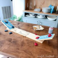 DIY tabletop cornhole board on a table with red and blue mini bean bags and snacks around it.