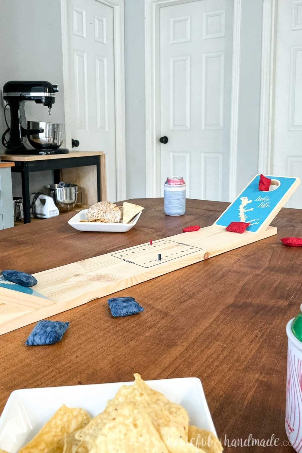 Looking across a dining table set for game night with snacks and a DIY tabletop cornhole game in the center.