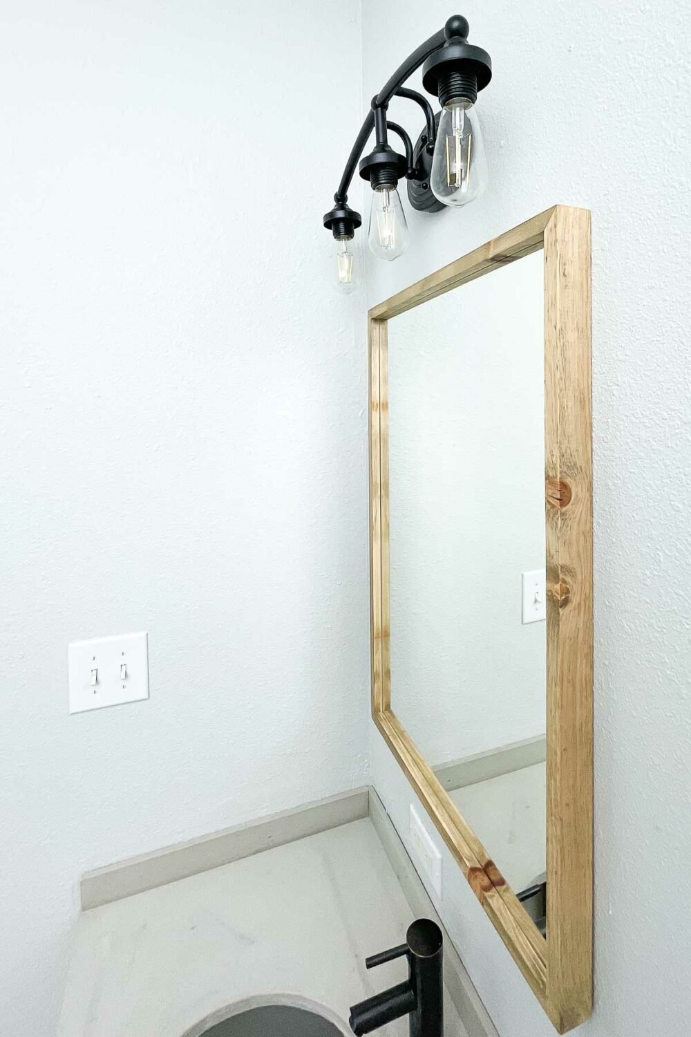 Looking at the side of the mirror in the bathroom on the light gray walls.