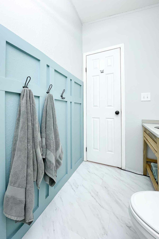 Looking toward the door of the small bathroom with board and batten wall and marble vinyl floor tiles.
