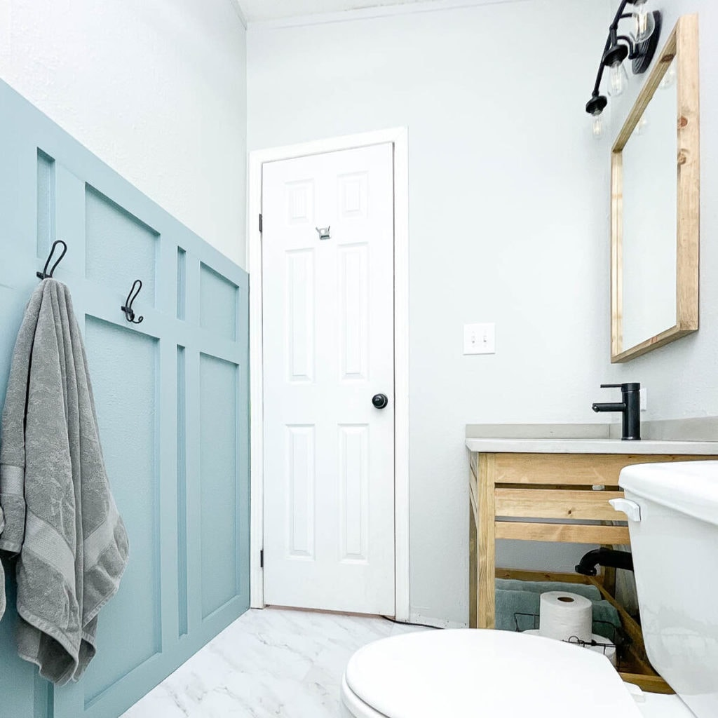 Small bathroom remodeled as part of the $100 Room Challenge with new vanity, floor and wall treatments.