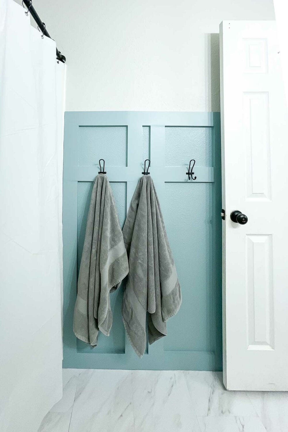 Blue painted board and batten wall in the bathroom with black hooks on it and gray towels hanging on 2 of the hooks.