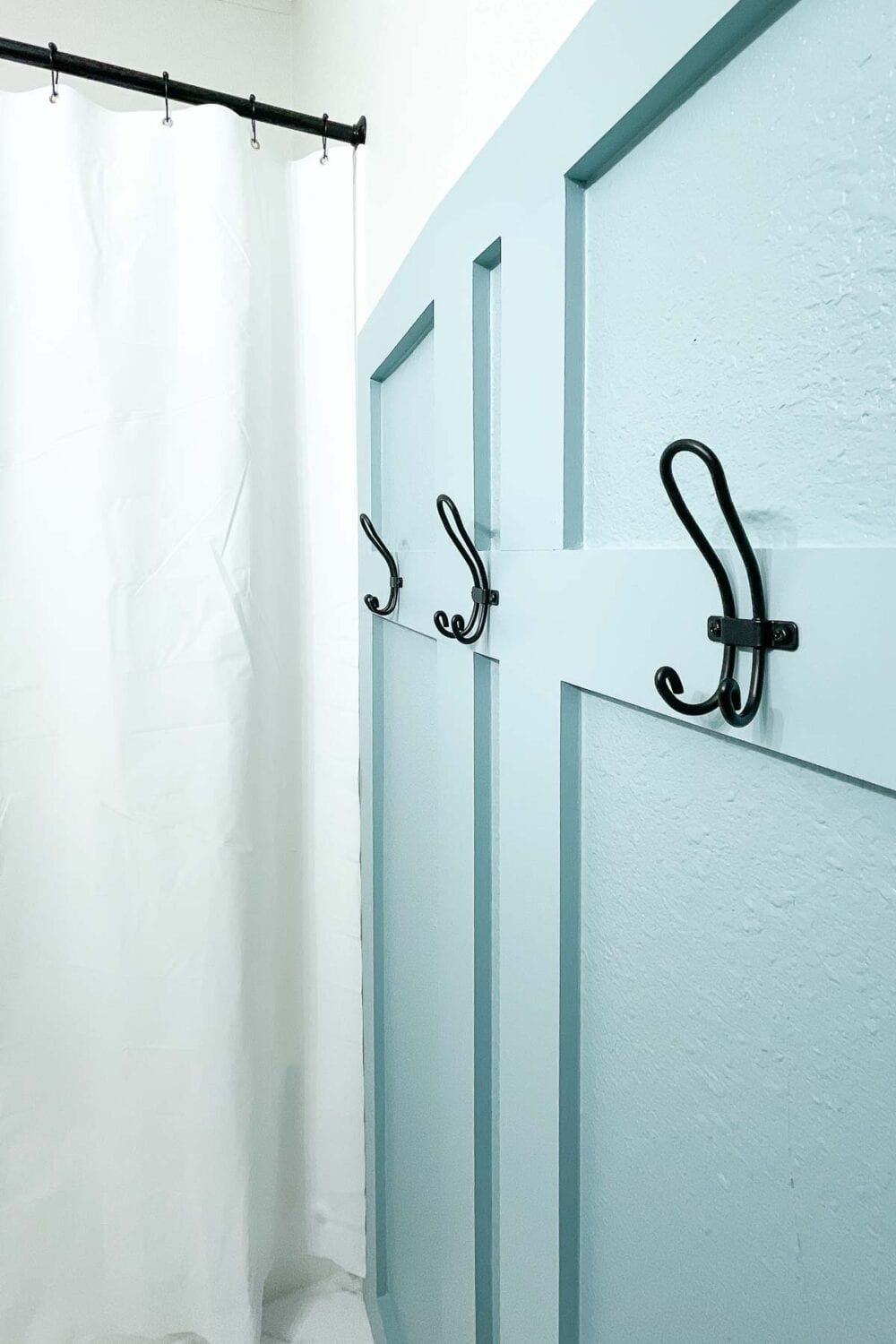 Close up of the 3 back hooks installed in the board and batten wall in the bathroom.