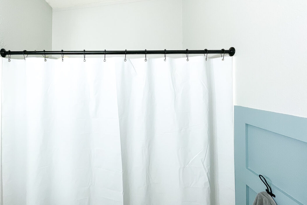 Black shower curtain rod with black rings holding a white shower curtain in the bathroom.