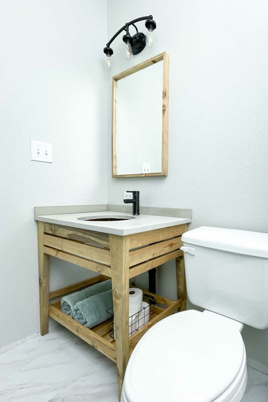 DIY open bathroom vanity in the budget bathroom remodel with a concrete countertop.