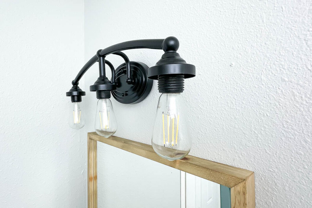 Black three bulb light fixture over the vanity mirror in the bathroom with no decorative glass and Edison bulbs inside.