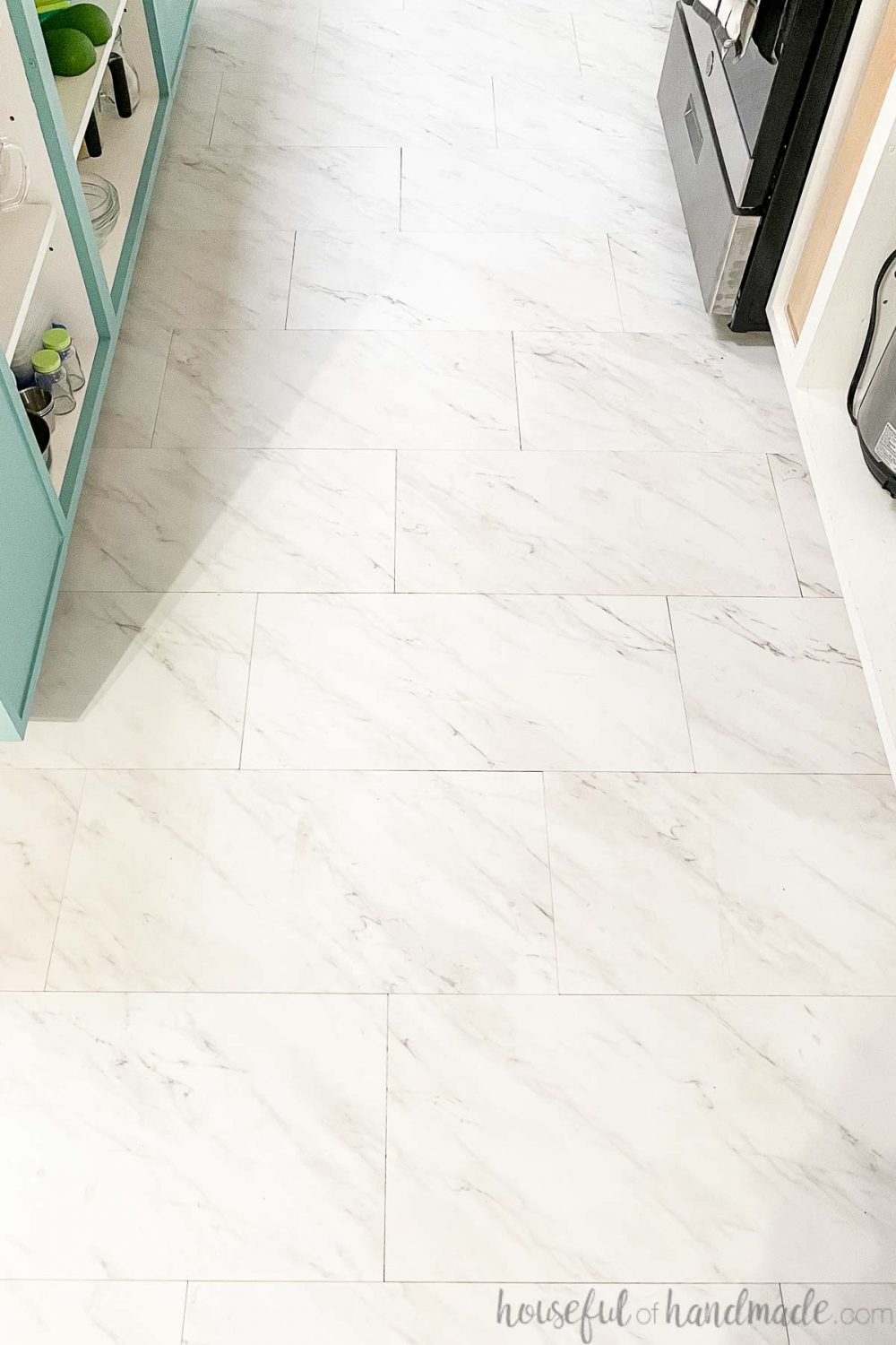 White vinyl tiles that look like marble laid in the kitchen between the sea green island and white cabinets.