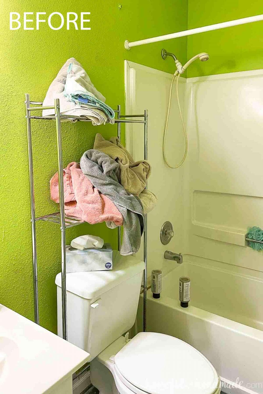 Picture of the green walls and metal shelving with poorly folded towels over the toilet.