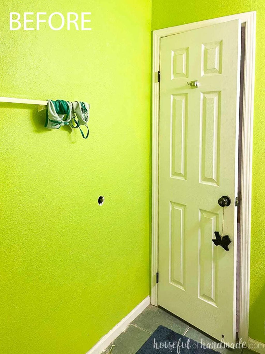 Before photo of the bathroom with electric green walls looking at the wall behind the white 6 panel door.