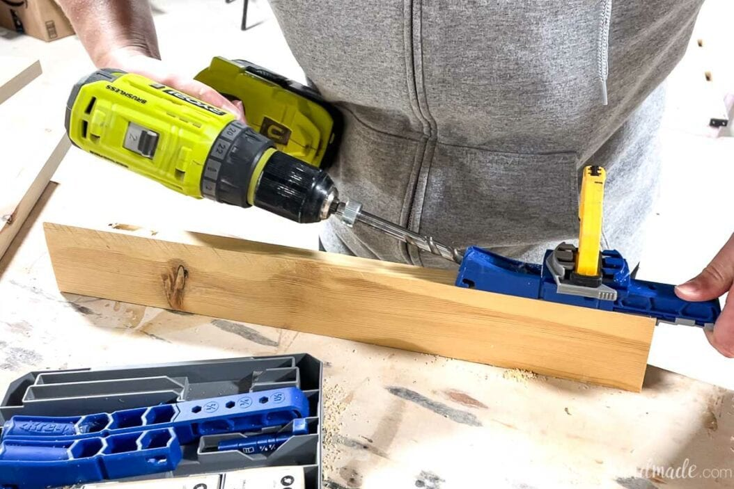 Drilling a pocket hole on the edge of the 1x3 board with the Kreg jig 320.