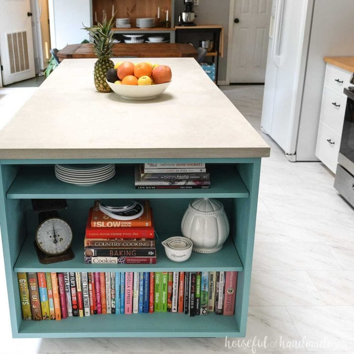 End view of the kitchen island with a concrete countertop and a dining room in the background.
