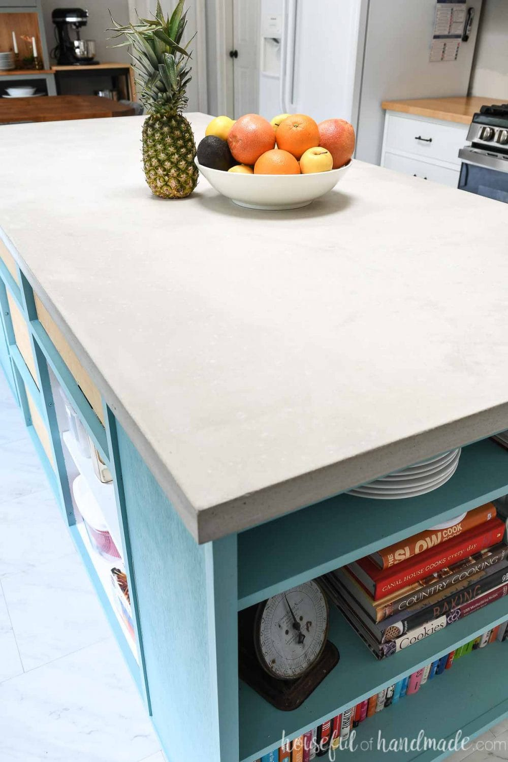 Looking down on the kitchen countertop made from light colored concrete on a blue kitchen island with a bookcase in it.